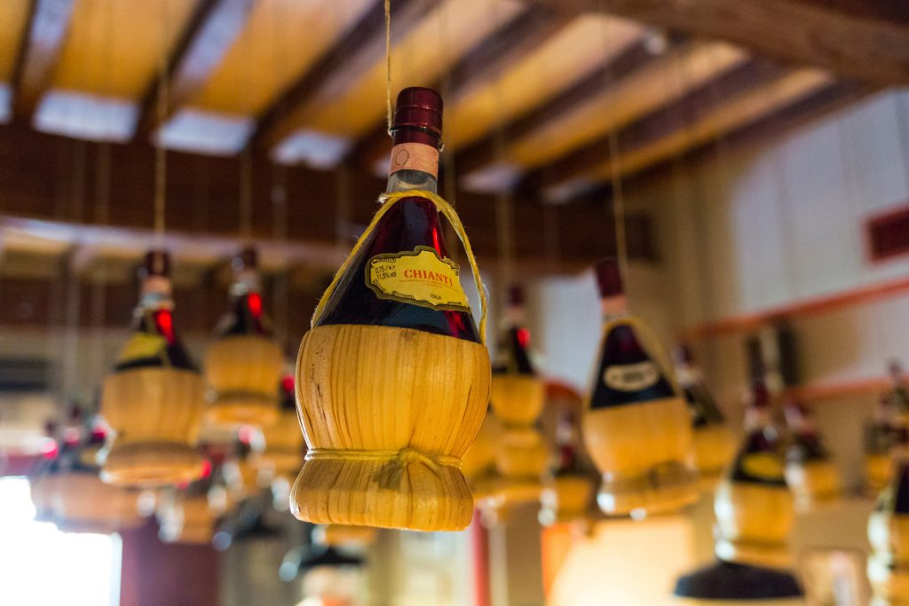 View of Chianti wine bottles hanging from the ceiling