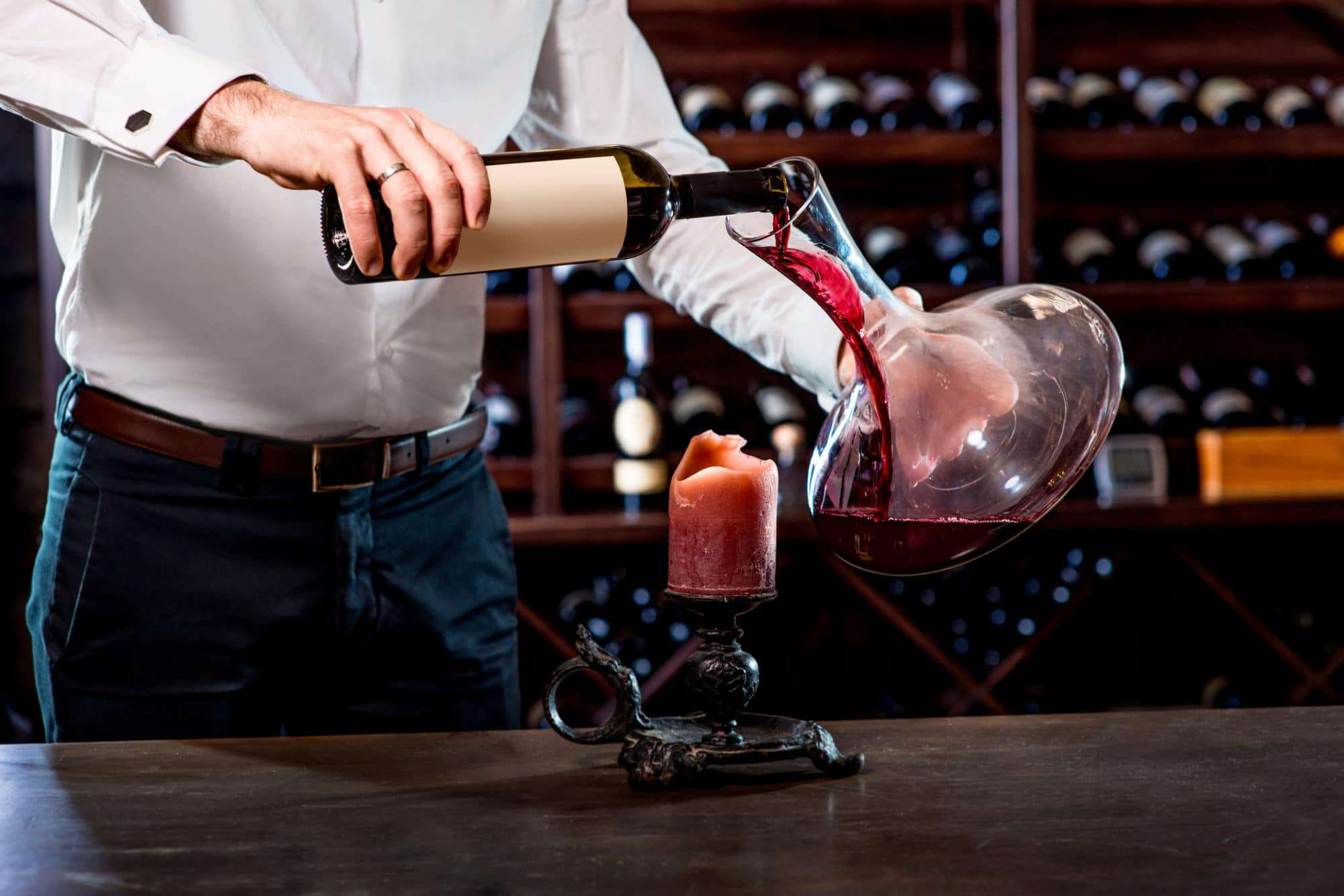 Sommelier pouring wine to the decanter in the wine cellar - wine decanters