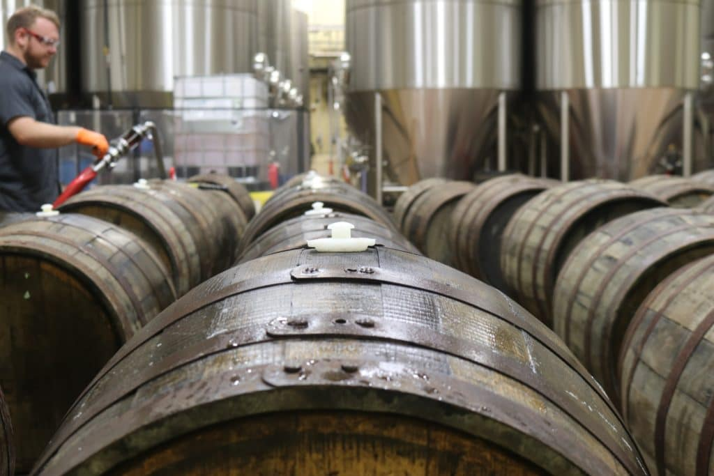 wine barrels with a winemaker in the background