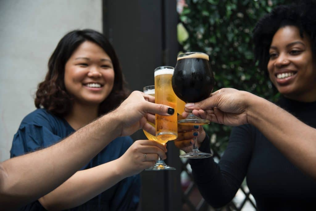 people toasting with glasses of beer