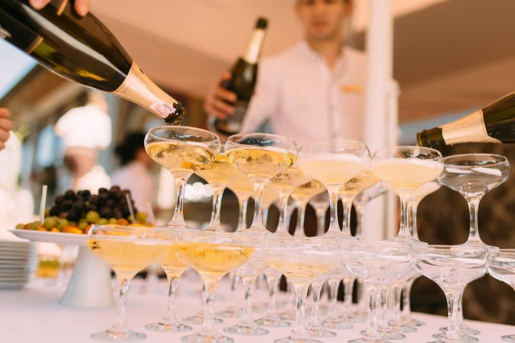 pouring champagne into stacked glasses