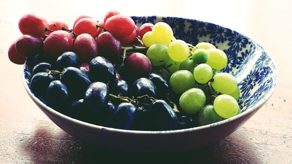 bowl of black, red, and green grapes