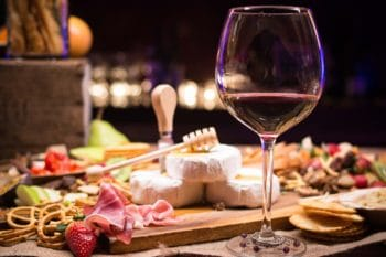 A glass of red wine with an assortment of cheeses and meats.