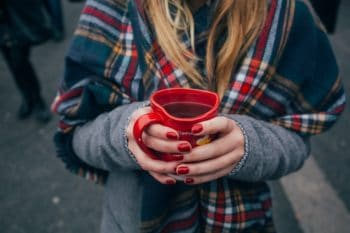 A person holding a red mug.