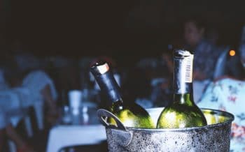 Two green wine bottle in a bucket.