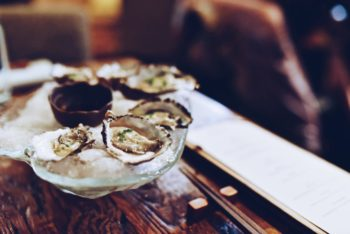 Some oysters on a wooden bar.