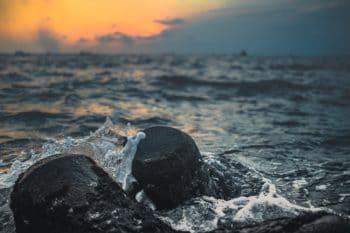 The ocean splashing water on some rocks.