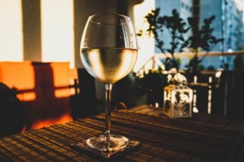 A glass of white wine on table.