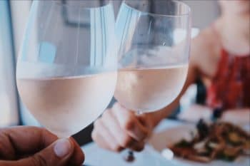 People toasting with rose in wine glasses.