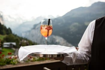 A person holding a glass of white sangria on a tray outdoors.