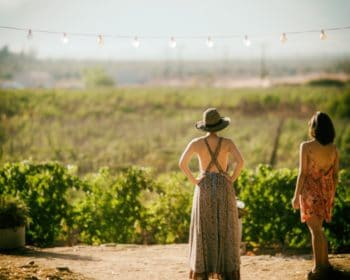 Two women standing by a vineyard.