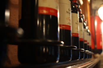 A row of red wine bottles on a shelf.