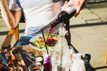 A person pouring wine into a wine glass.