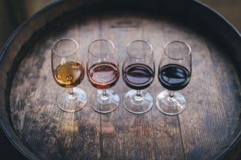 Four wine classes on an oak barrel.