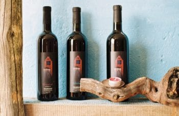 Three bottles of wine on a shelf.